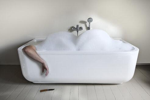 Mid adult man in bathtub with knife - FMKYF000316