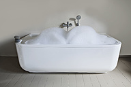 Bathtub with soapsuds and pebbles in bathroom - FMKYF000291