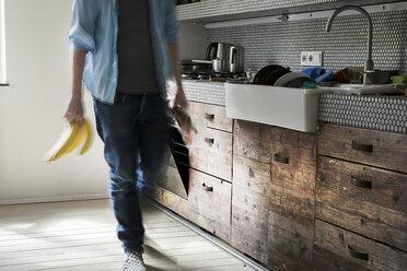 Mature man in kitchen holding bananas - FMKYF000300
