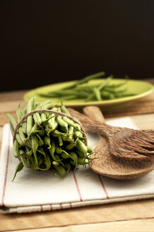Bush beans with wooden spoon and napkin on wooden table, close up - OD000060