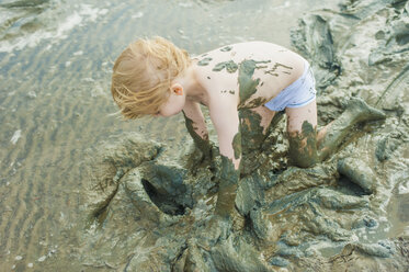 Germany, Schleswig Holstein, Boy playing in mud at beach - MJF000209