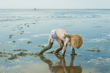 Germany, Schleswig Holstein, Boy playing in mud at beach - MJF000221