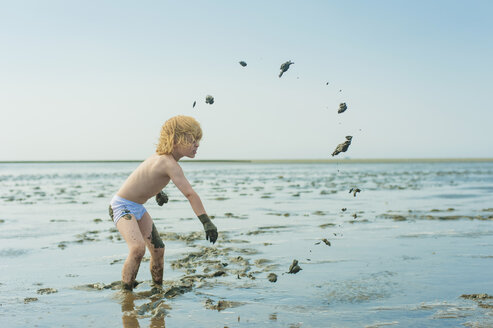Germany, Schleswig Holstein, Boy playing in mud at beach - MJF000223