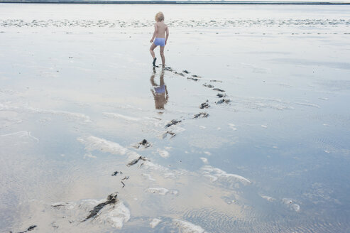 Germany, Schleswig Holstein, Boy playing in mud at beach - MJF000224