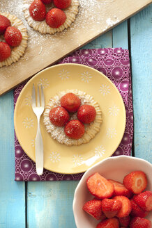 Strawberry tartlets on plate besides bowl of strawberry, close up - OD000085