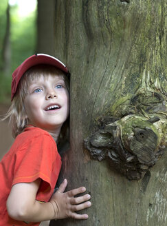 Austria, Boy leaning on tree trunk, smiling - CW000061