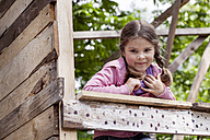 Germany, North Rhine Westphalia, Cologne, Portrait of girl playing in playground, smiling - FMKYF000391