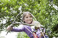 Germany, North Rhine Westphalia, Cologne, Girl sitting on bicycle at playground, smiling - FMKYF000372