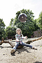 Germany, North Rhine Westphalia, Cologne, Girl playing with ball in playground - FMKYF000401