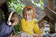 Germany, North Rhine Westphalia, Cologne, Boys listening music in playground, smiling - FMKYF000429