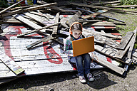 Germany, North Rhine Westphalia, Cologne, Girl using laptop and listening music with head phone - FMKYF000378