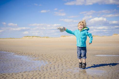 Denmark, Romo, Boy jumping at North Sea, smiling - MJF000226