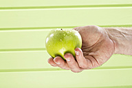 Mature man holding granny smith against green background, close up - MAEF006885