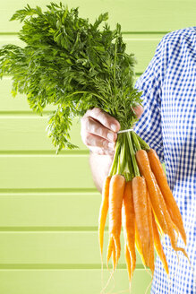 Mature man holding bunch of carrots against green background, close up - MAEF006882