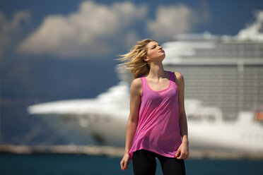 Greece, Young woman posing in front of cruise ship - AJF000014