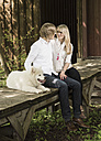 Germany, Bavaria, Couple sitting with dog and looking at each other - CAF000018