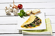 Omelette with mushrooms on wooden table - MAEF006897