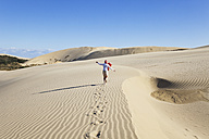 New Zealand, Mature woman running on Te Paki Giant Sand Dunes - GW002303