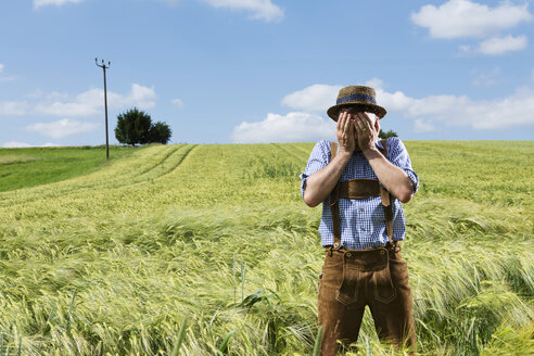 Germany, Bavaria, Farmer covering his face in field - MAEF006902
