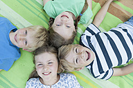 Germany, Bavaria, four smiling children lying on a blanket - NH001377