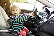 Germany, Bonn, Baby boy sitting in car and holding steering wheel - MF000533
