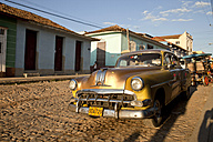 Cuba, Us car on cobblestone street - PC000013