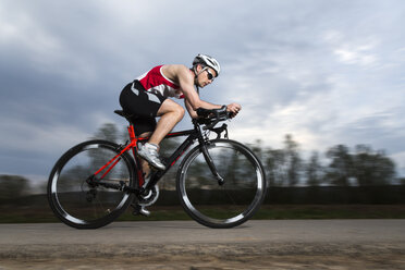 Germany, triathlete riding bicycle - STSF000059