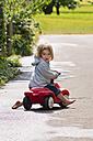 Germany, Baden Wuerttemberg, Girl sitting on bobby car - LVF000138