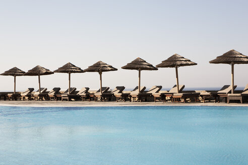 Greece, Mykonos, Empty chairs and sunshade at pool - SK001364