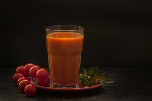 Glass of tomato juice with cherry tomatoes on wooden table, close up - OD000173