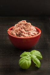 Bowl of tuna with herb on wooden table, close up - OD000188