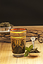 Peppermint tea in glass and ladle on wooden table - OD000201