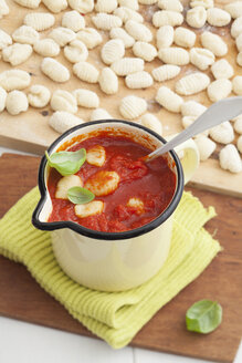 Homemade gnocchi with tomato sauce on chopping board - ECF000254