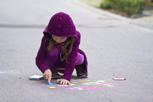 Germany, Girl drawing on street with chalk - SARF000049