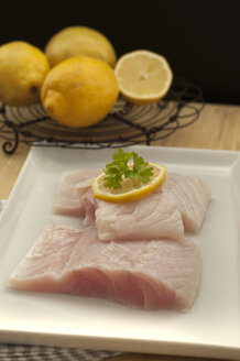 Red fish in tray with lemon on wooden table, close up - OD000192