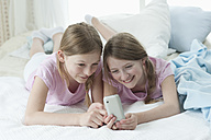 Germany, Bavaria, Girls using smart phone on bed, smiling - CRF002444