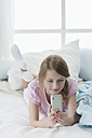 Germany, Bavaria, Girl using smart phone on bed, smiling - CRF002449