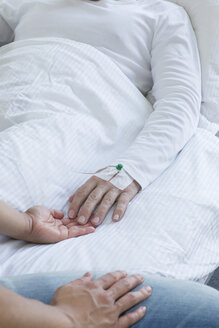 Germany, Freiburg, Woman holding hand of man in hospital, close up - DRF000023