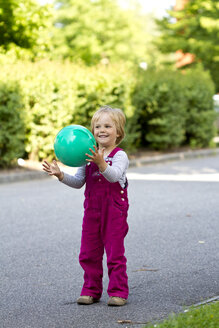 Germany, Kiel, Girl catching green ball, smiling - JFEF000142