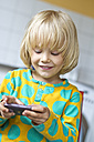Germany, Kiel, Girl playing with smartphone, smiling - JFE000155