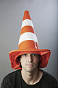 Portrait of young man with traffic cone on his head, close up - JAT000107