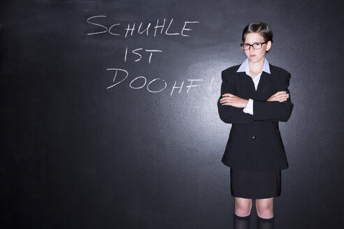 Girl standing in front of blackboard - MAEF006924