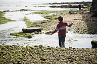 Great Britain, Scotland, Fife, Anstuther, boy at the beach throwing stones into water - SBDF000194