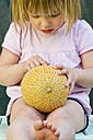 Germany, Bavaria, Girl holding galia melon, close up - LVF000155
