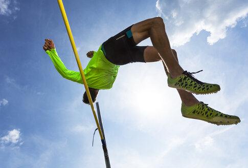 Germany, Man athlete jumping Hurdles on track - STSF000060