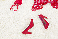 Red High Heels and red inner wear laying on white carpet - DRF000026