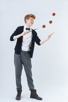 Young man showing magic with ball, smiling - TCF003495