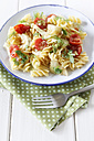 Plate of fennel tomato pasta on wooden table, close up - EVGF000156