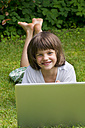 Germany, Rhineland Palatinate, Kaiserslautern, Portrait of girl with laptop in garden, smiling - LV000163