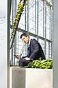 Germany, Hannover, Businessman using smart phone - KFF000199